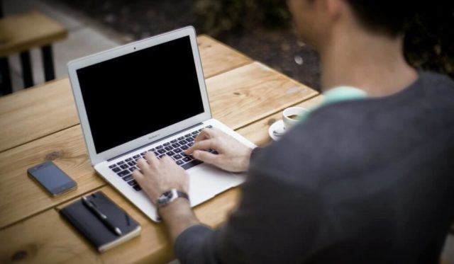 Mann Tippt auf seinem Laptop