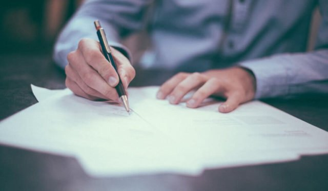 Mann Schreibt mit einem Stift auf Papier
